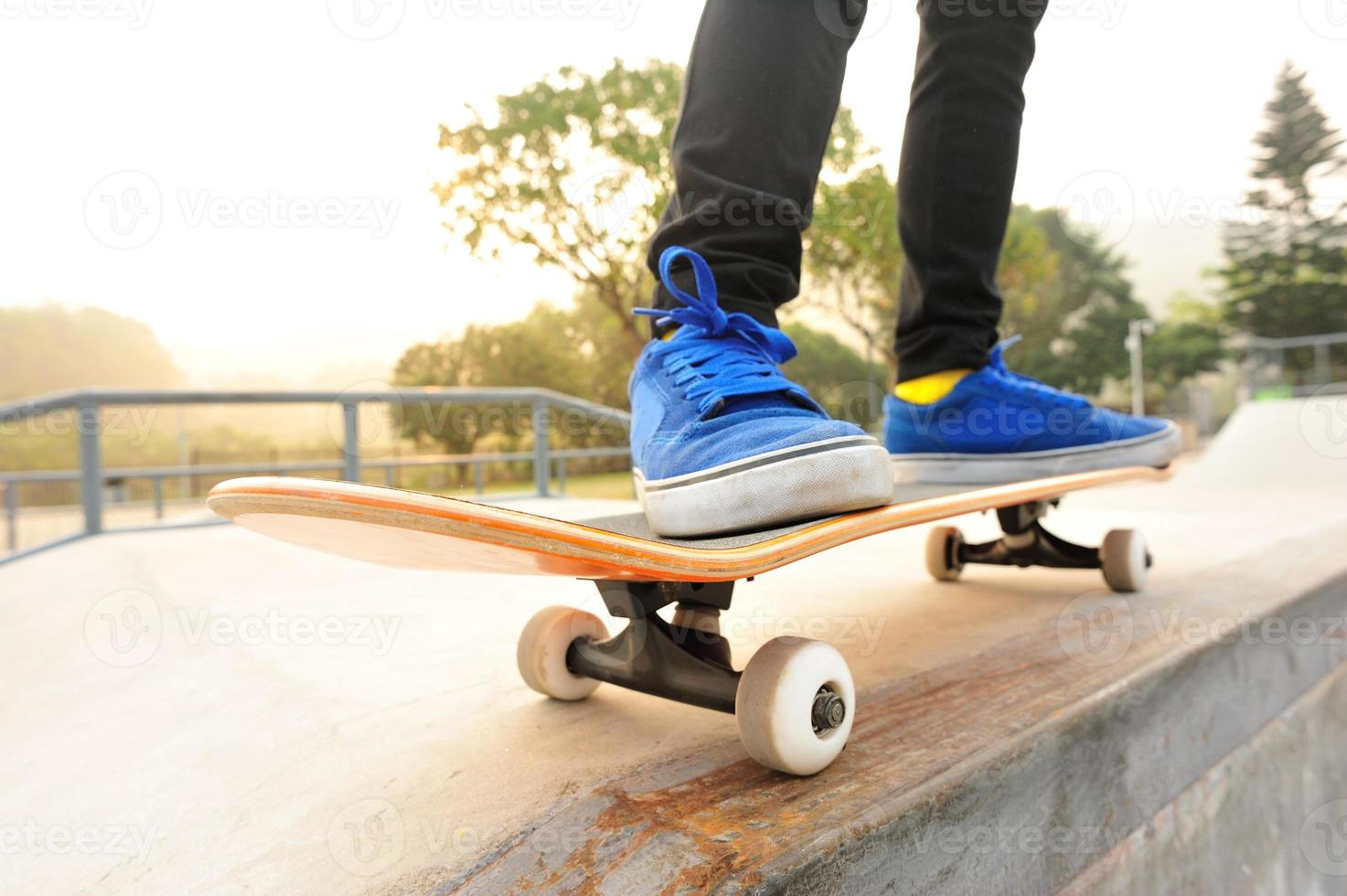 gambe in scarpe da ginnastica su uno skateboard foto