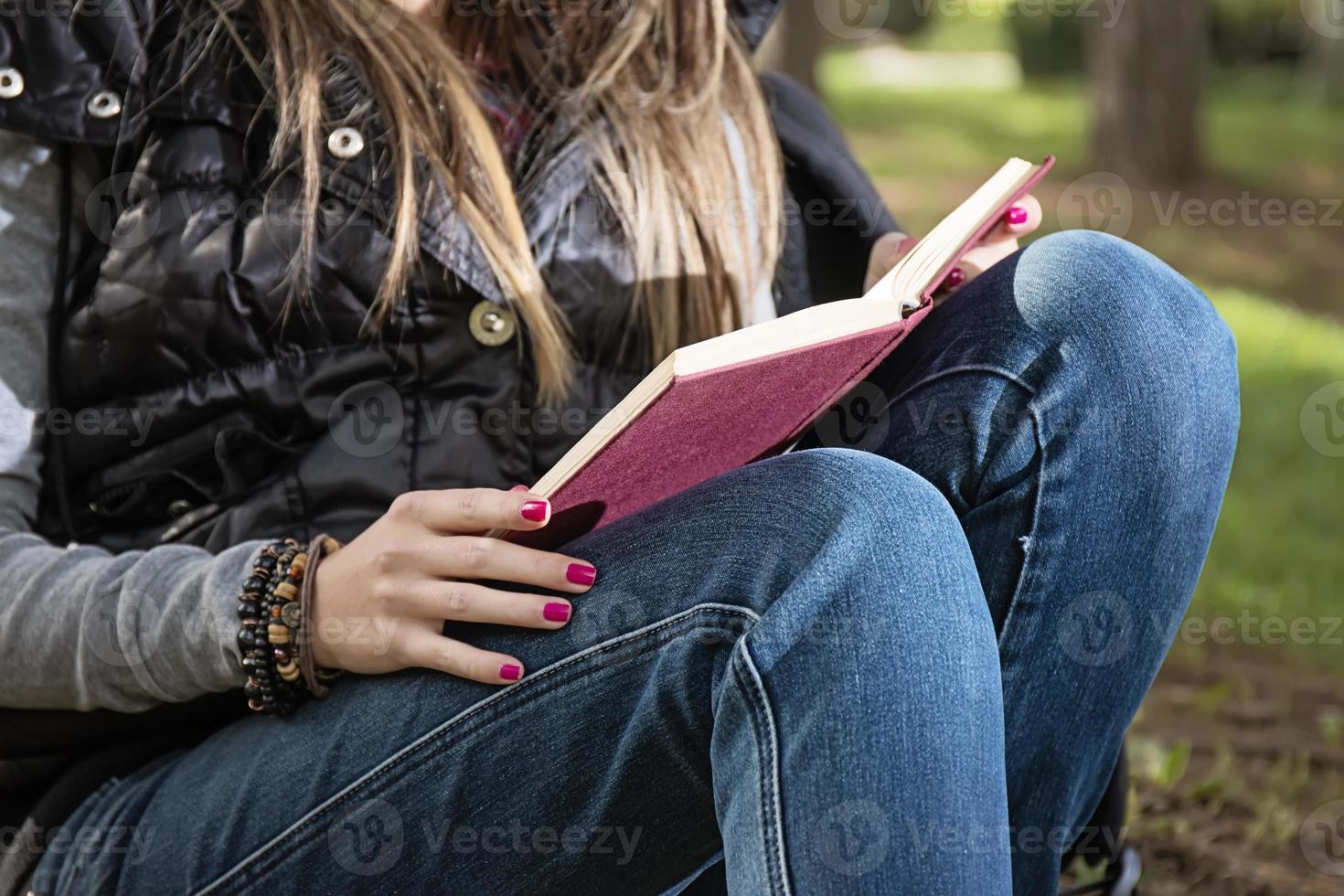 bella ragazza che legge un libro nel parco in autunno foto