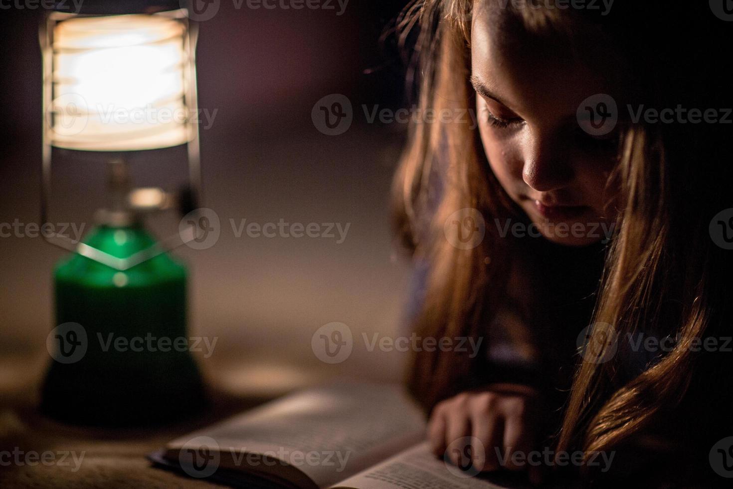 libro di lettura della ragazza nella lampada di illuminazione foto