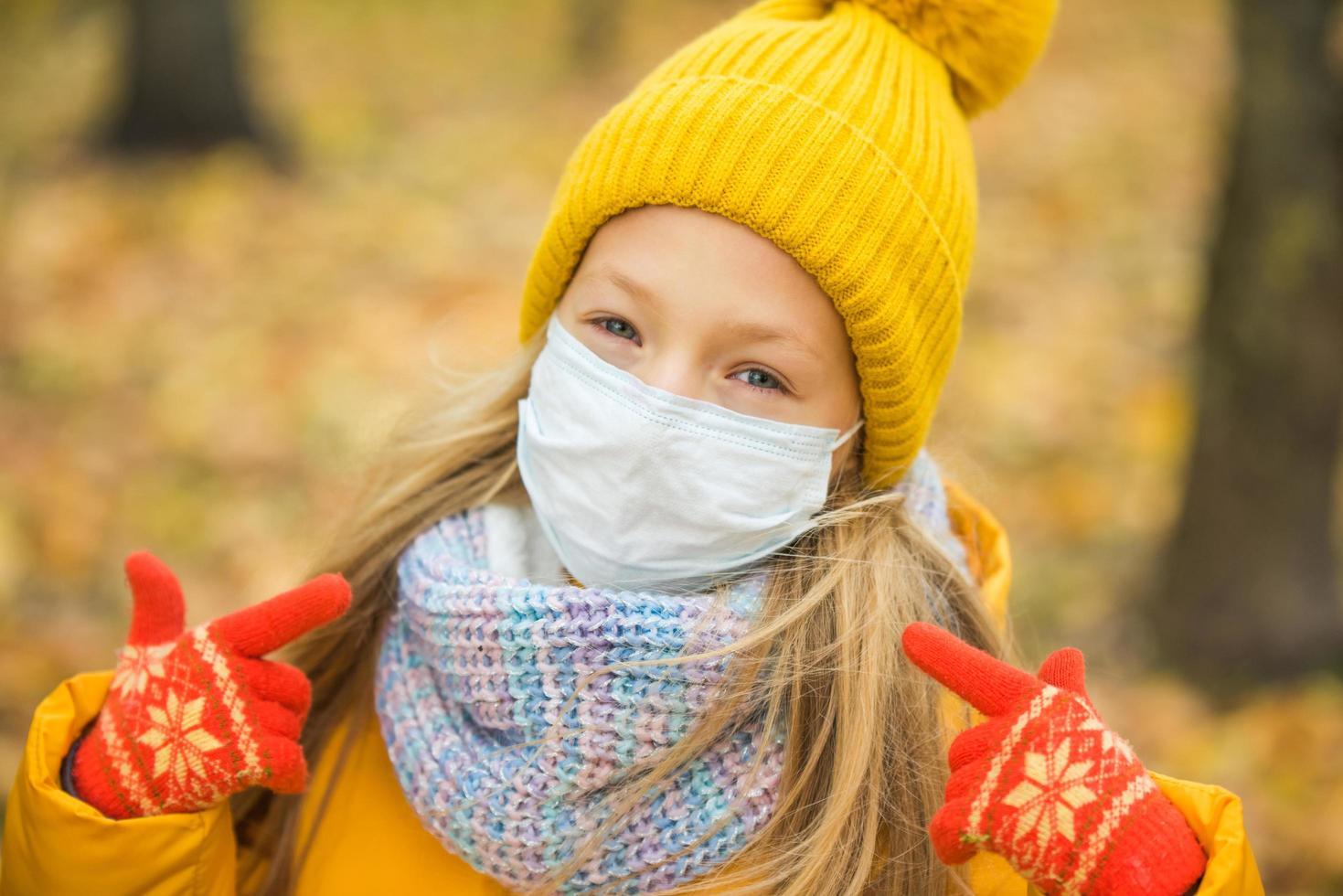 ragazza che indossa la maschera per il viso e abiti invernali foto