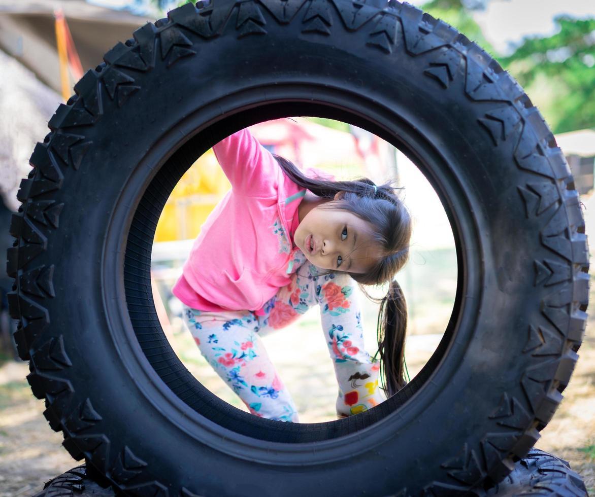piccola ragazza asiatica guardando attraverso un pneumatico foto