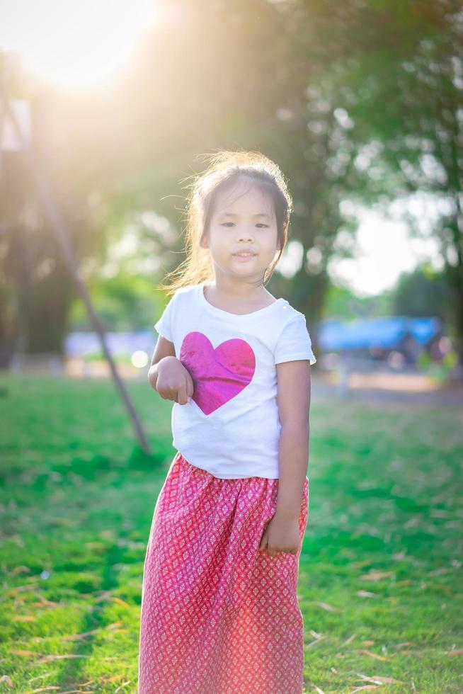 felice ragazza asiatica in piedi nel parco foto
