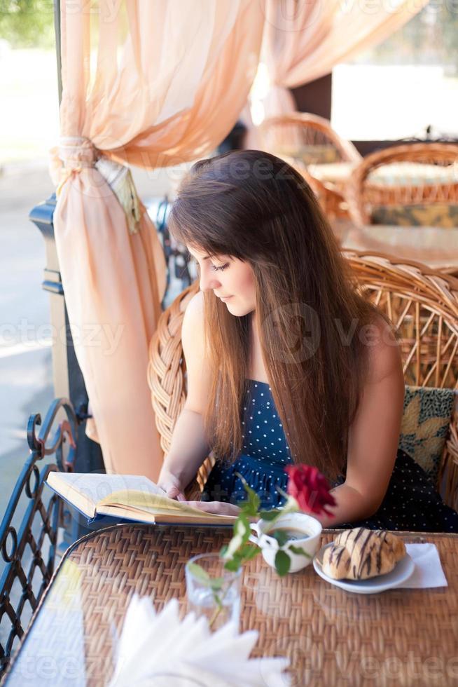 bella donna che legge un libro nella caffetteria foto
