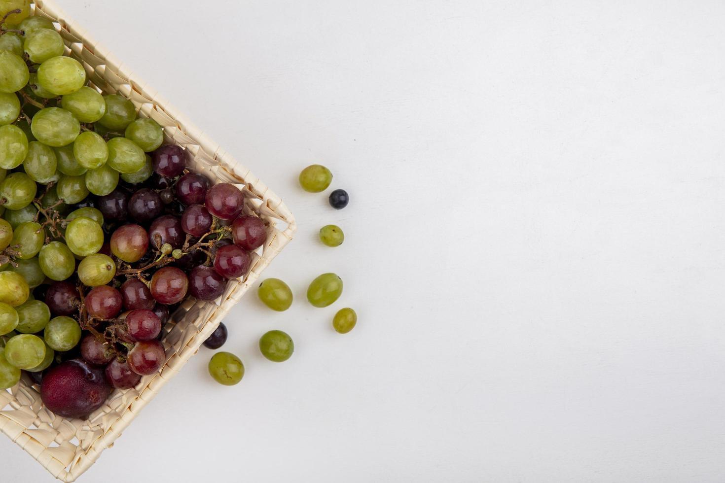 frutta assortita in un cesto su sfondo neutro foto