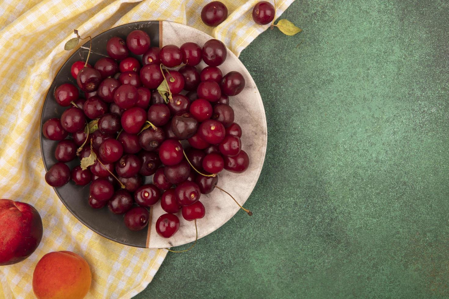 piatto di ciliegie su sfondo verde con copia spazio foto