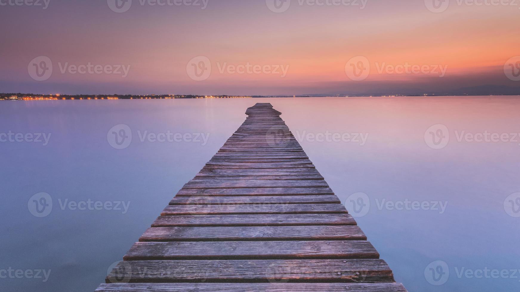 lungo pontile in legno sul lago di garda al tramonto foto