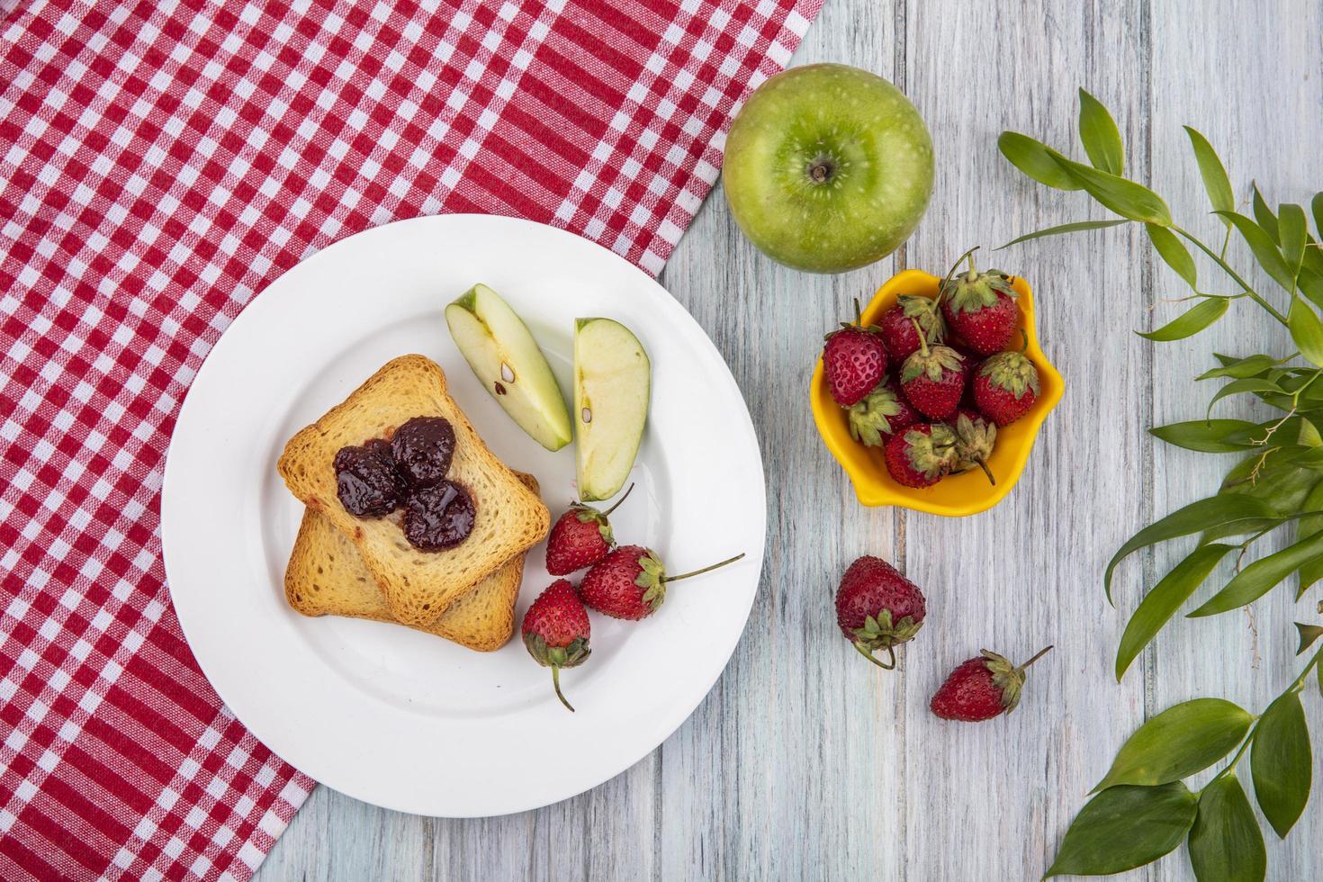 toast con frutta sul panno plaid rosso su fondo in legno foto