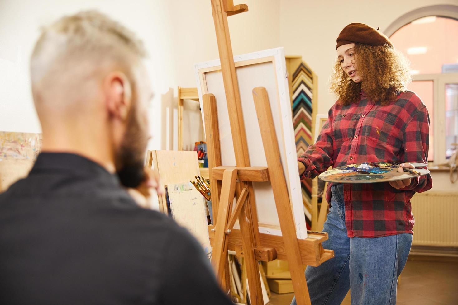 ragazza riccia sta disegnando un ritratto di un uomo foto