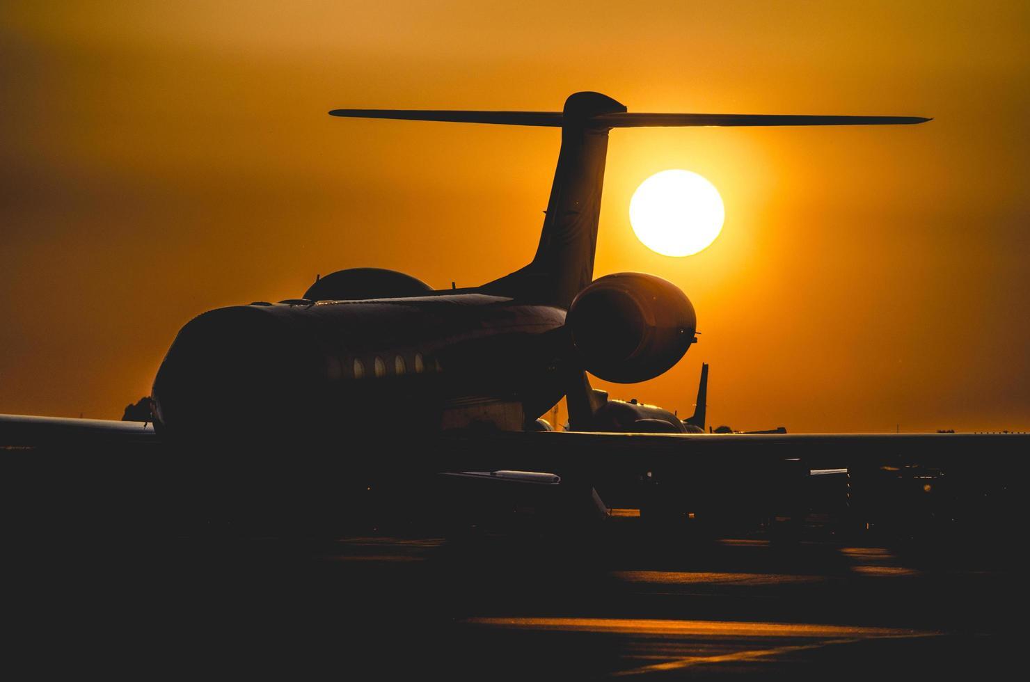 silhouette di aeroplano durante il tramonto foto