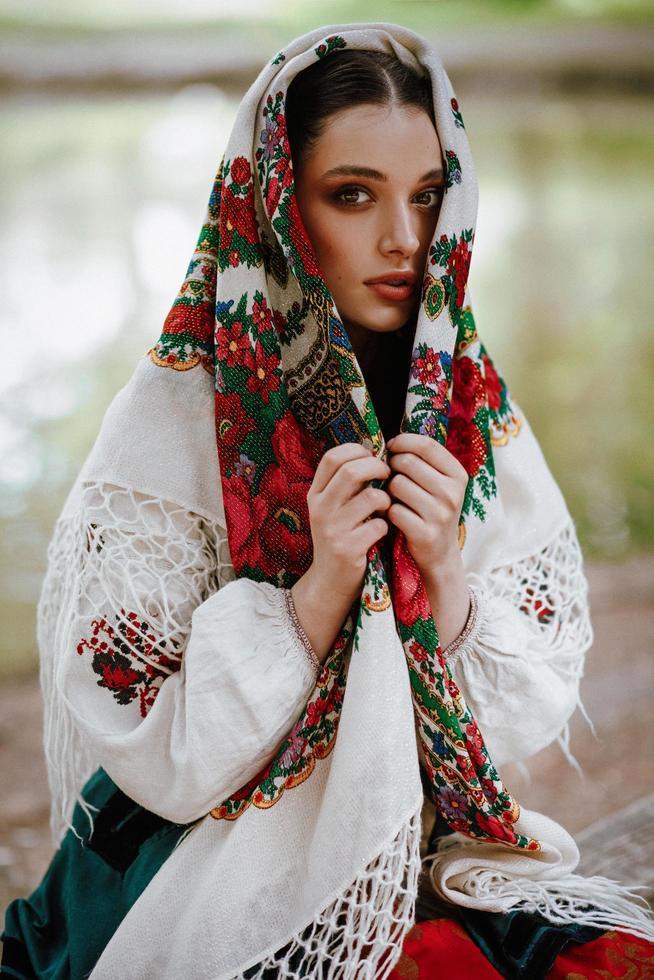 bella ragazza in un abito etnico tradizionale con uno scialle ricamato foto
