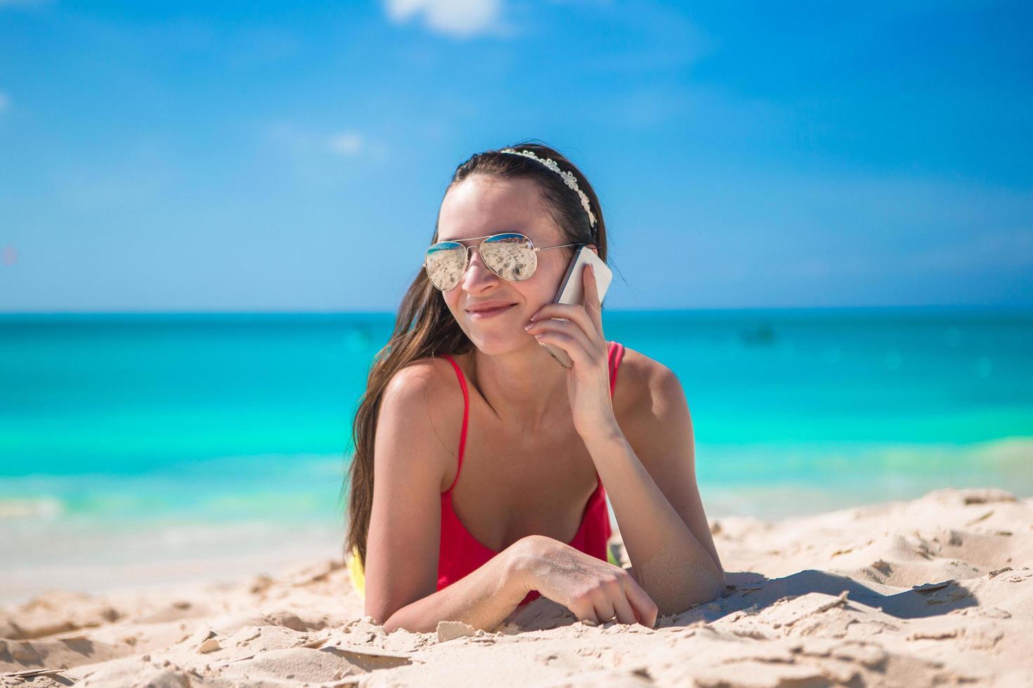 donna sdraiata sulla spiaggia e parlando dal suo telefono foto