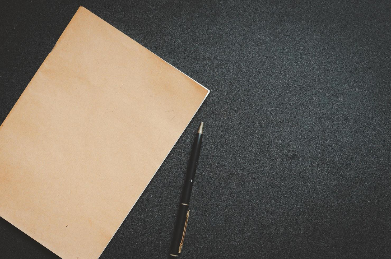 blocco note marrone e penna su una scrivania nera foto