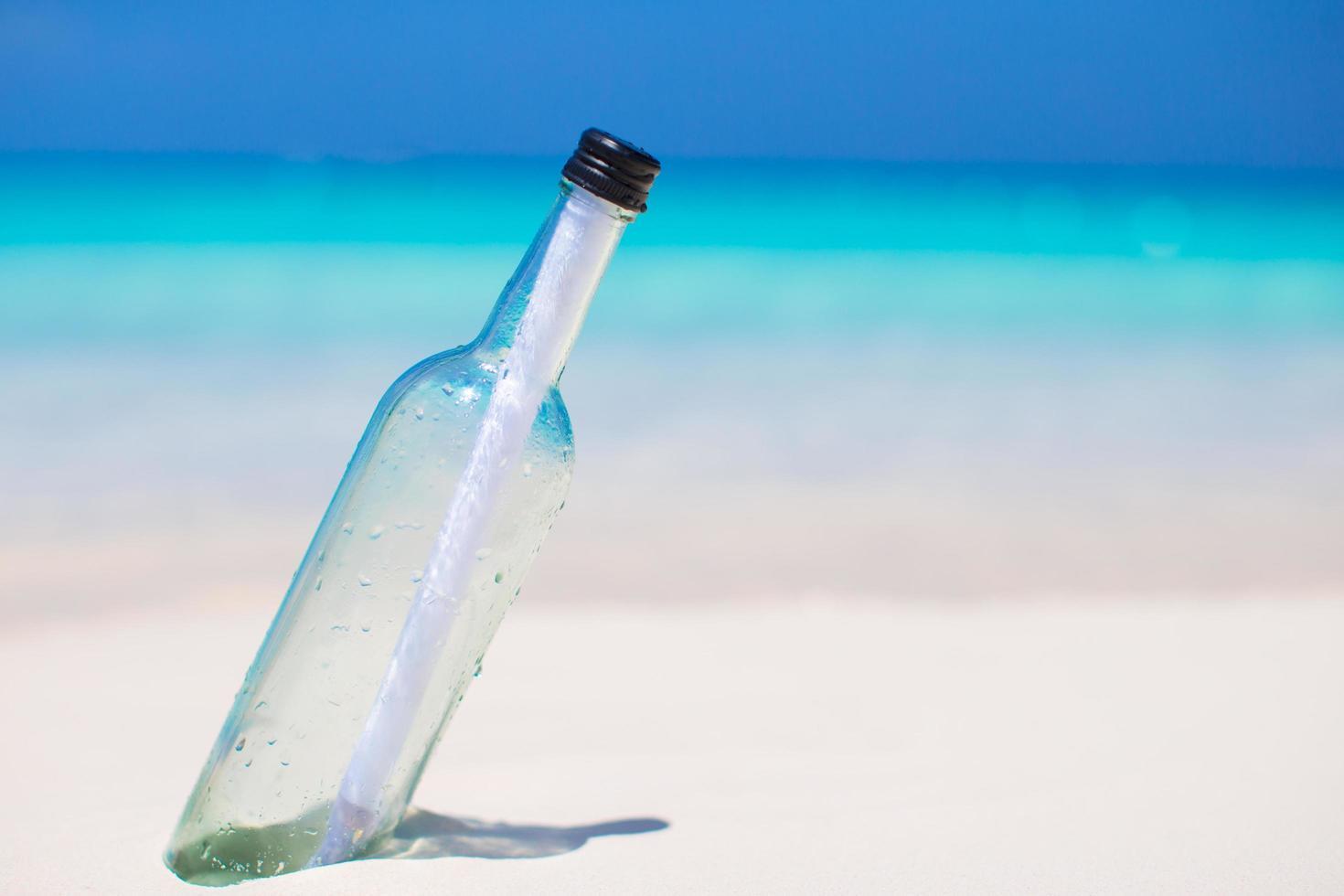 bottiglia con un messaggio sulla sabbia bianca foto