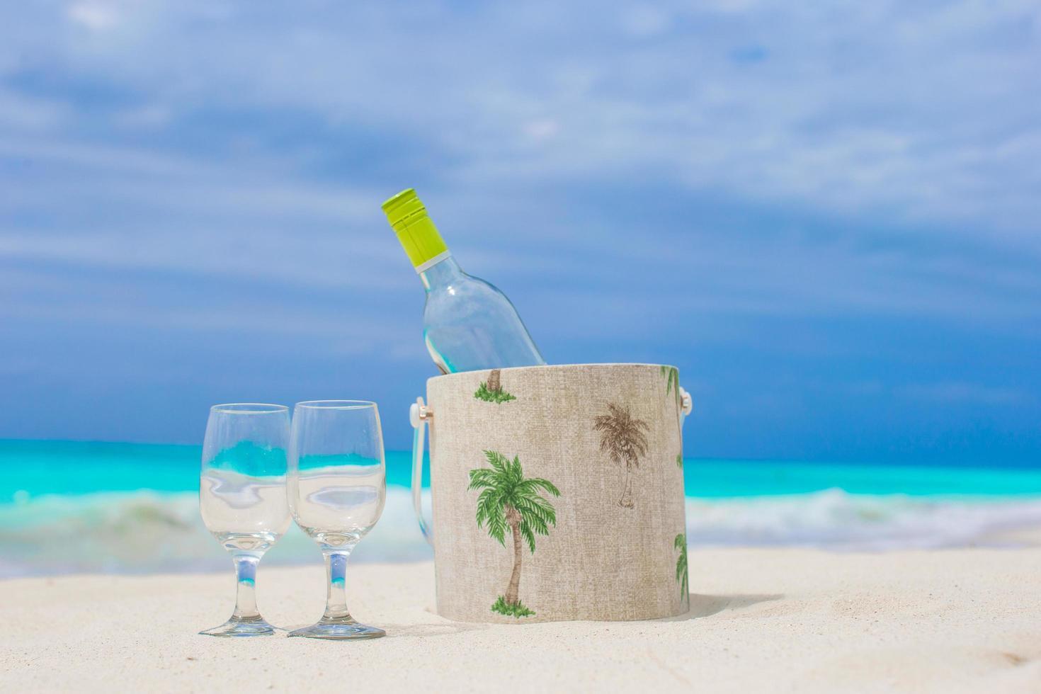 bottiglia di vino bianco e due bicchieri sulla spiaggia foto