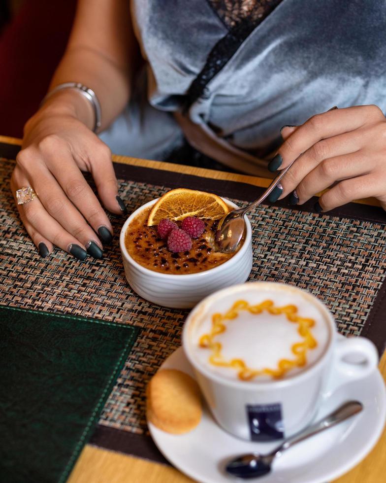 donna che mangia dessert lampone con caffè latte foto
