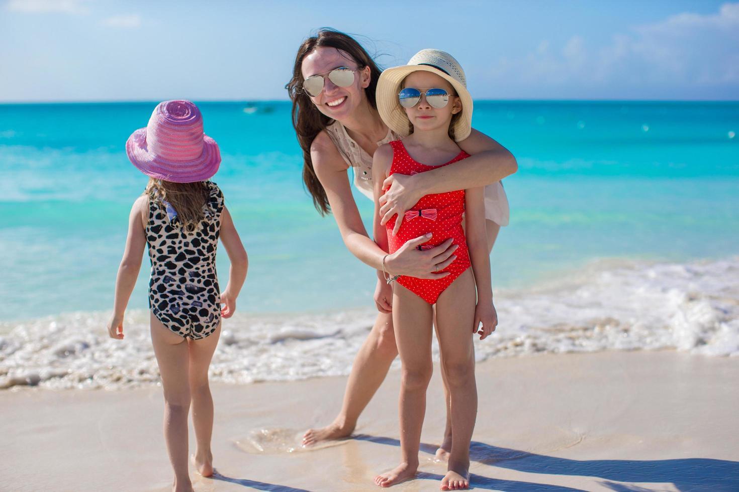 madre e due bambini su una spiaggia foto