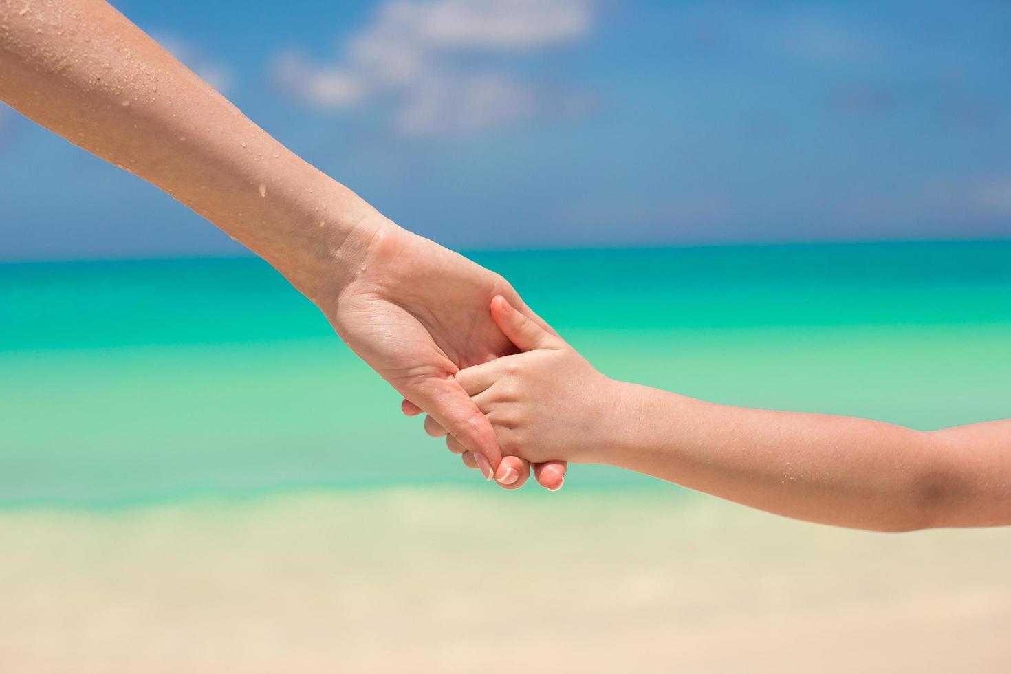 genitore e figlio che tengono le mani su una spiaggia foto