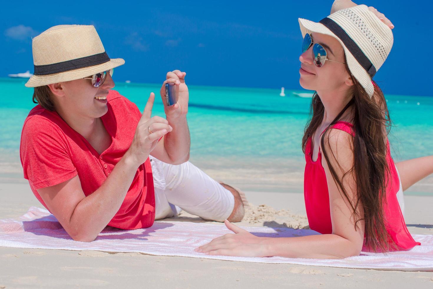 uomo che scatta una foto di una donna su una spiaggia