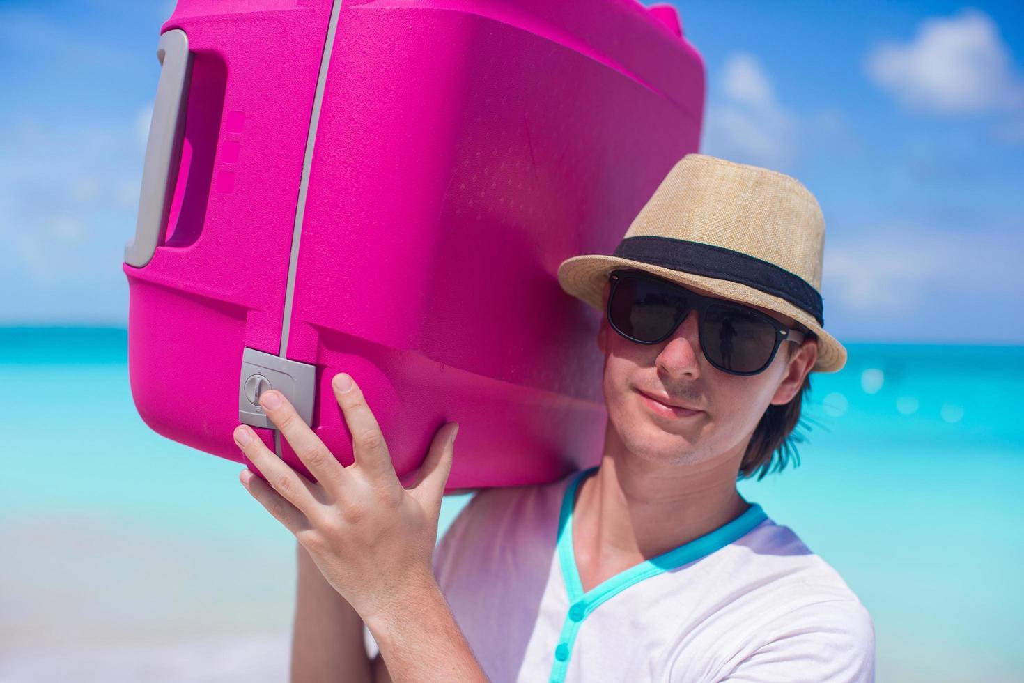 uomo che trasporta bagagli su una spiaggia foto