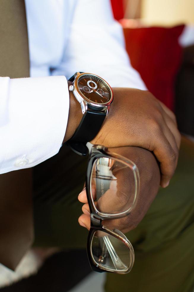persona che tiene gli occhiali e indossa un orologio da polso foto