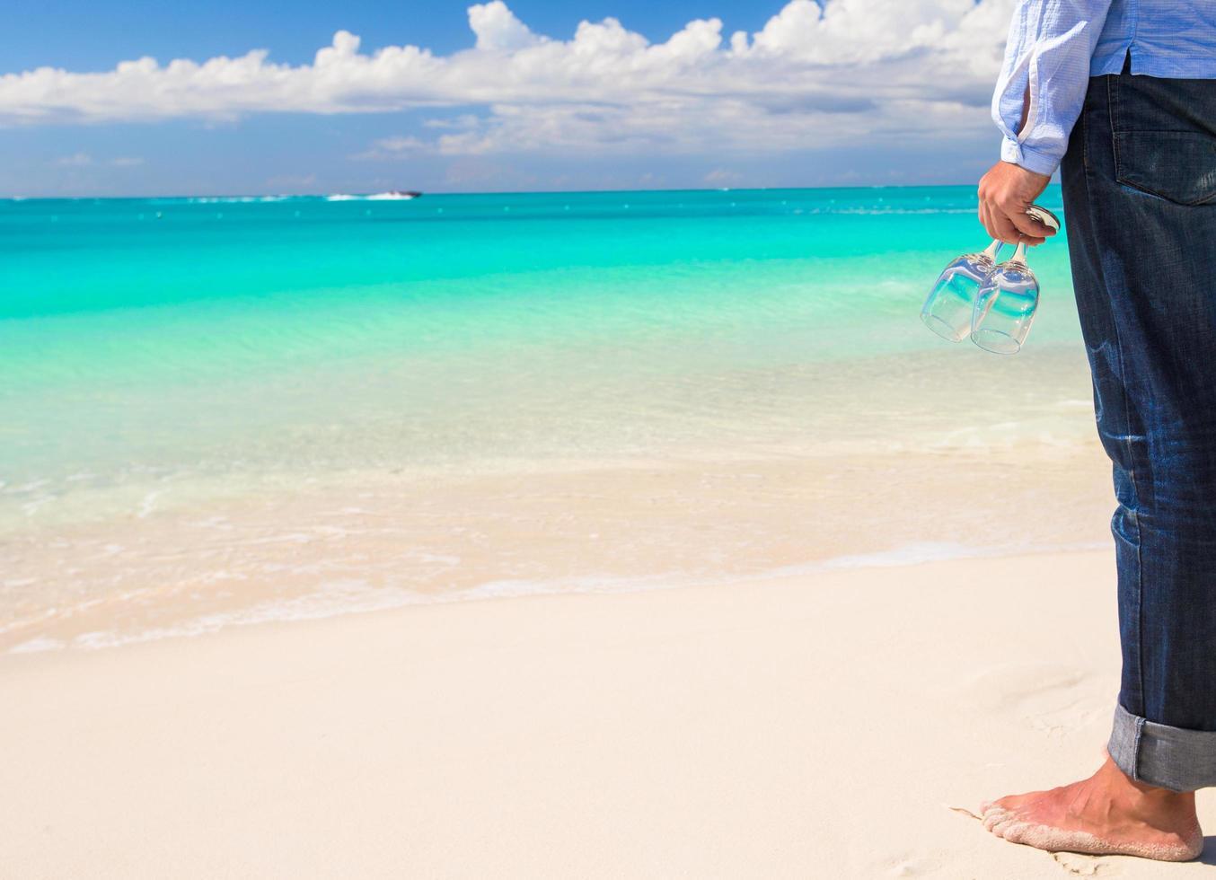 uomo con bicchieri di vino su una spiaggia tropicale foto