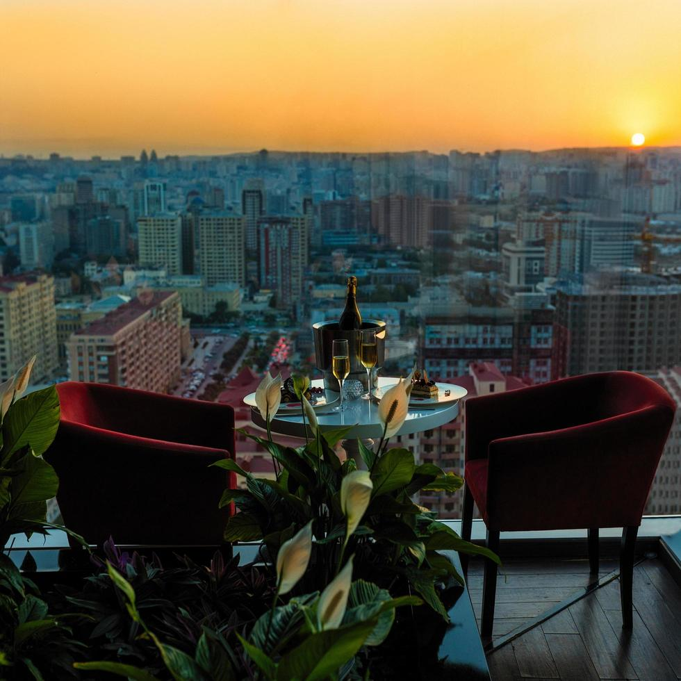 bottiglia di champagne e bicchieri al ristorante con vista sulla città al tramonto foto