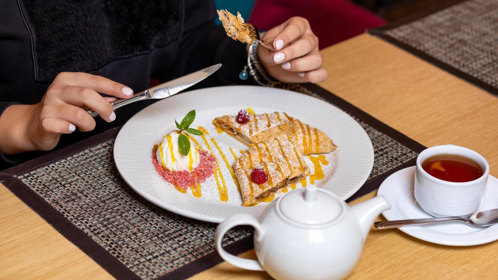 donna che mangia il dessert con il tè foto