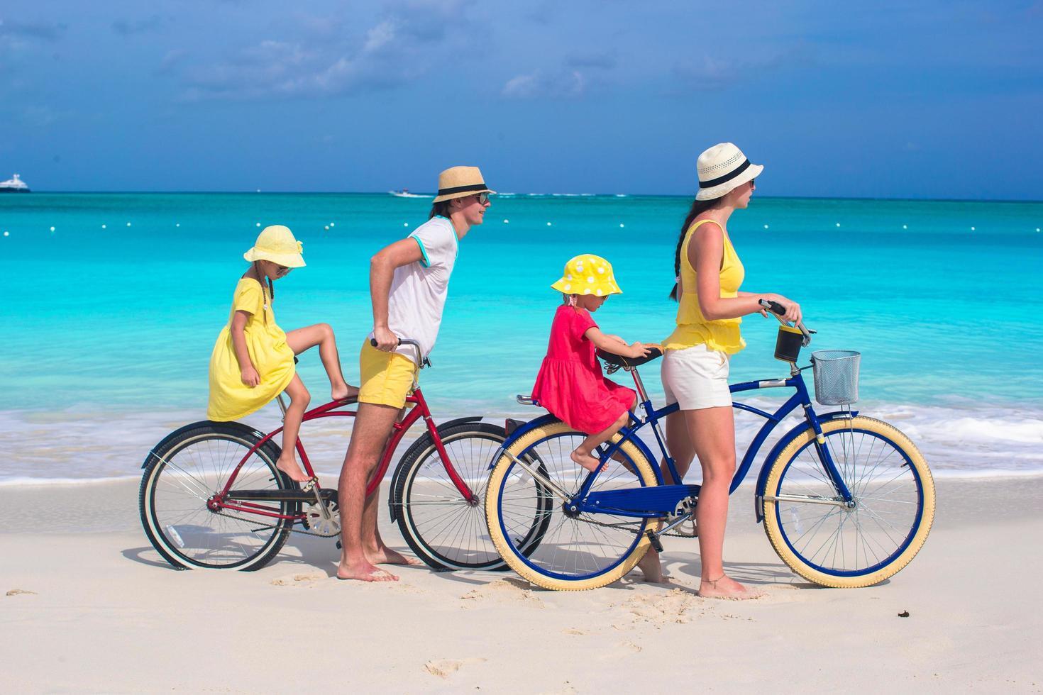 giovani genitori e bambini che vanno in bicicletta su una spiaggia foto