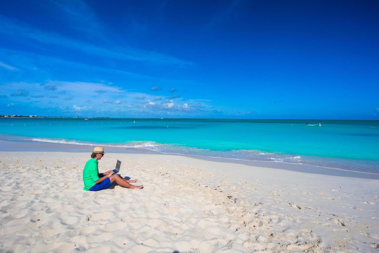 uomo che utilizza un computer portatile sulla spiaggia foto