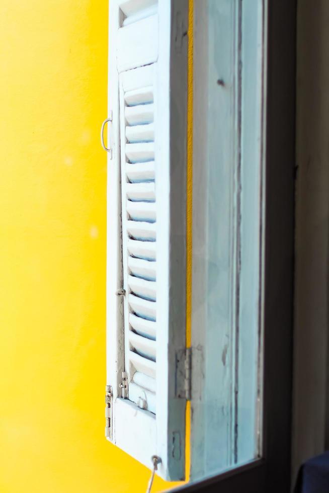 aprire la finestra vintage in legno bianco vicino al muro giallo foto