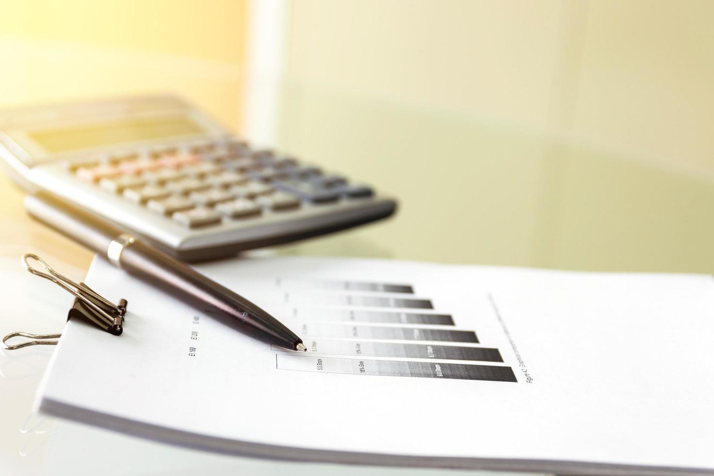 soft focus di una penna e una calcolatrice con scartoffie foto