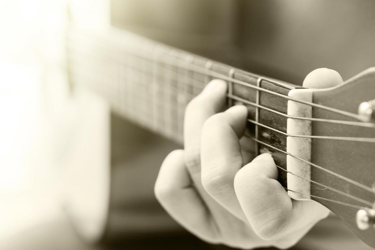 primo piano delle mani che giocano una chitarra acustica foto