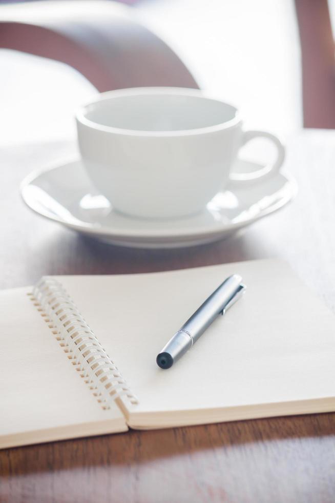 taccuino in bianco con penna su un tavolo di legno foto