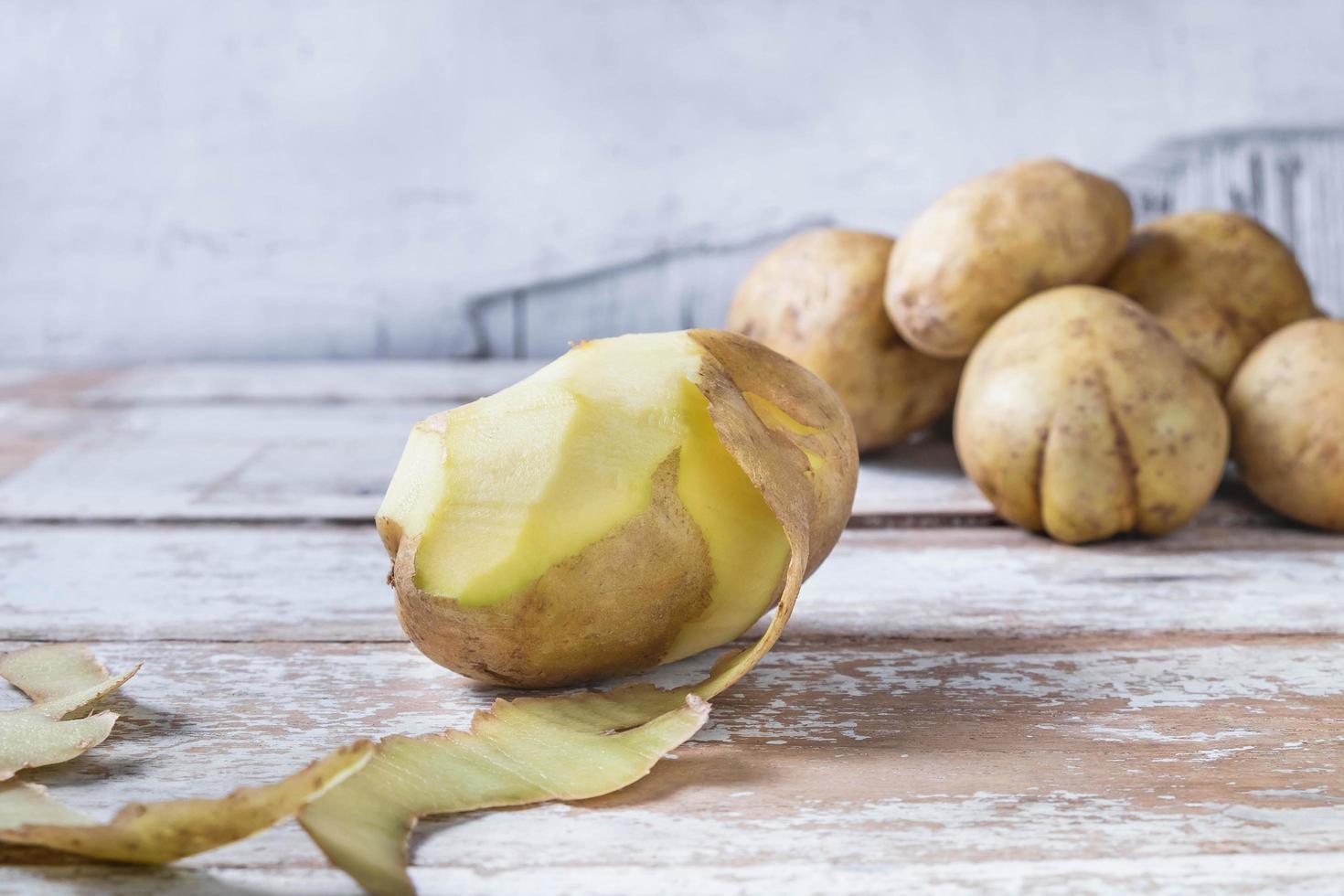 le patate vengono sbucciate su fondo in legno foto