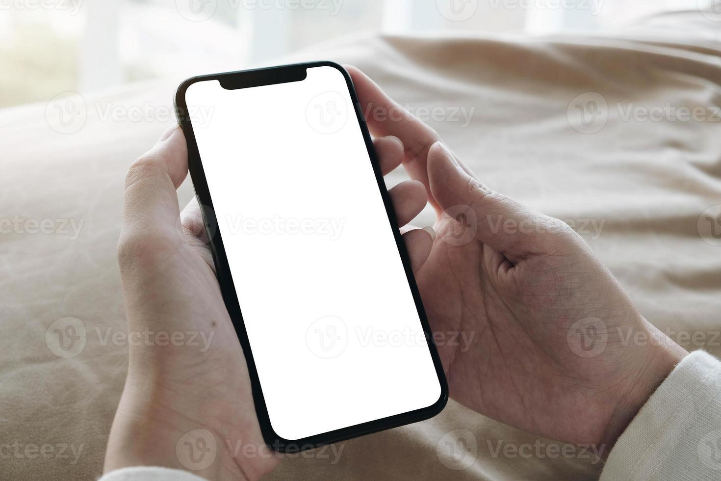 vista dall'alto della donna che tiene il telefono cellulare con schermo vuoto foto