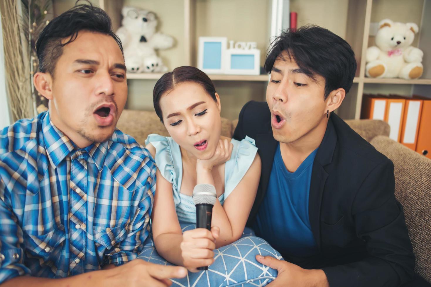 gruppo di amici che cantano una canzone insieme nel loro soggiorno foto