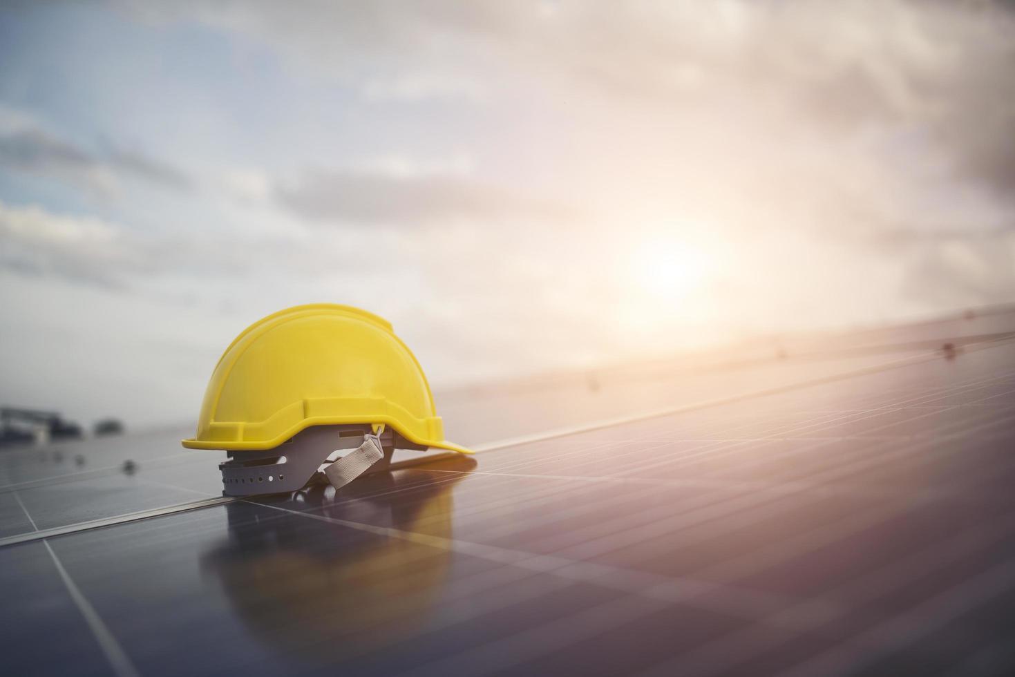 casco di sicurezza giallo sul pannello solare foto