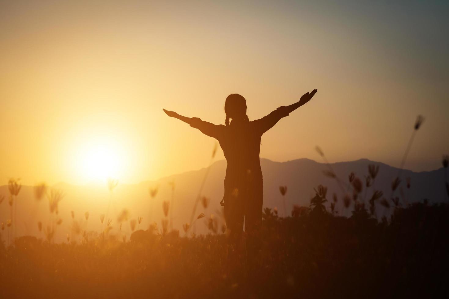 silhouette di una donna che prega su uno sfondo di bel cielo foto