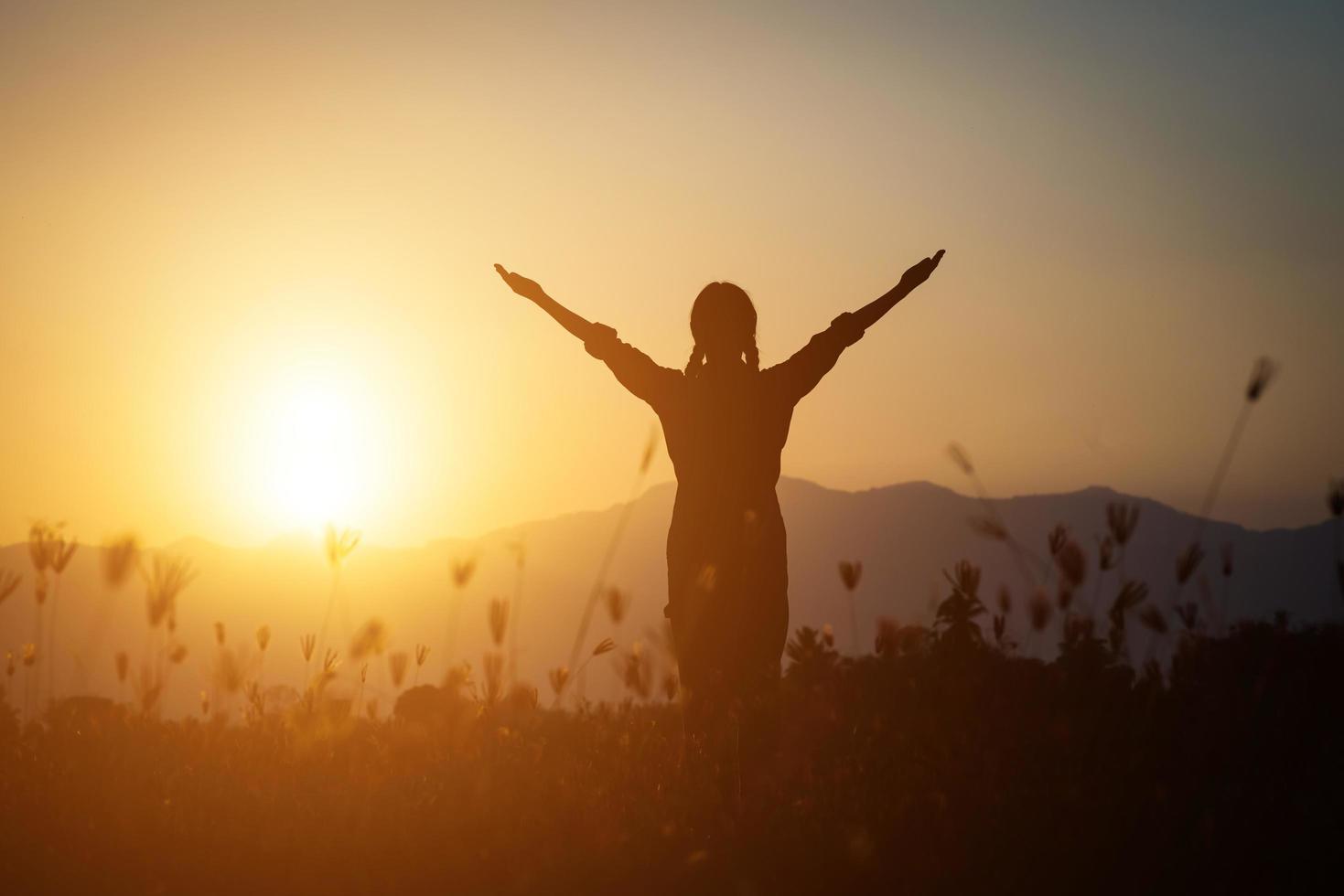 silhouette di una donna che prega su uno sfondo di cielo foto