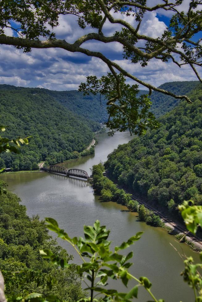 ponte su un fiume tra le montagne verdi foto