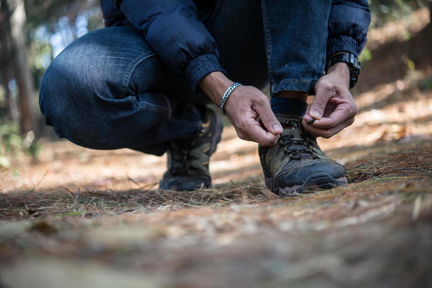 giovane escursionista allaccia i lacci delle scarpe mentre è in viaggio con lo zaino in spalla nella foresta foto