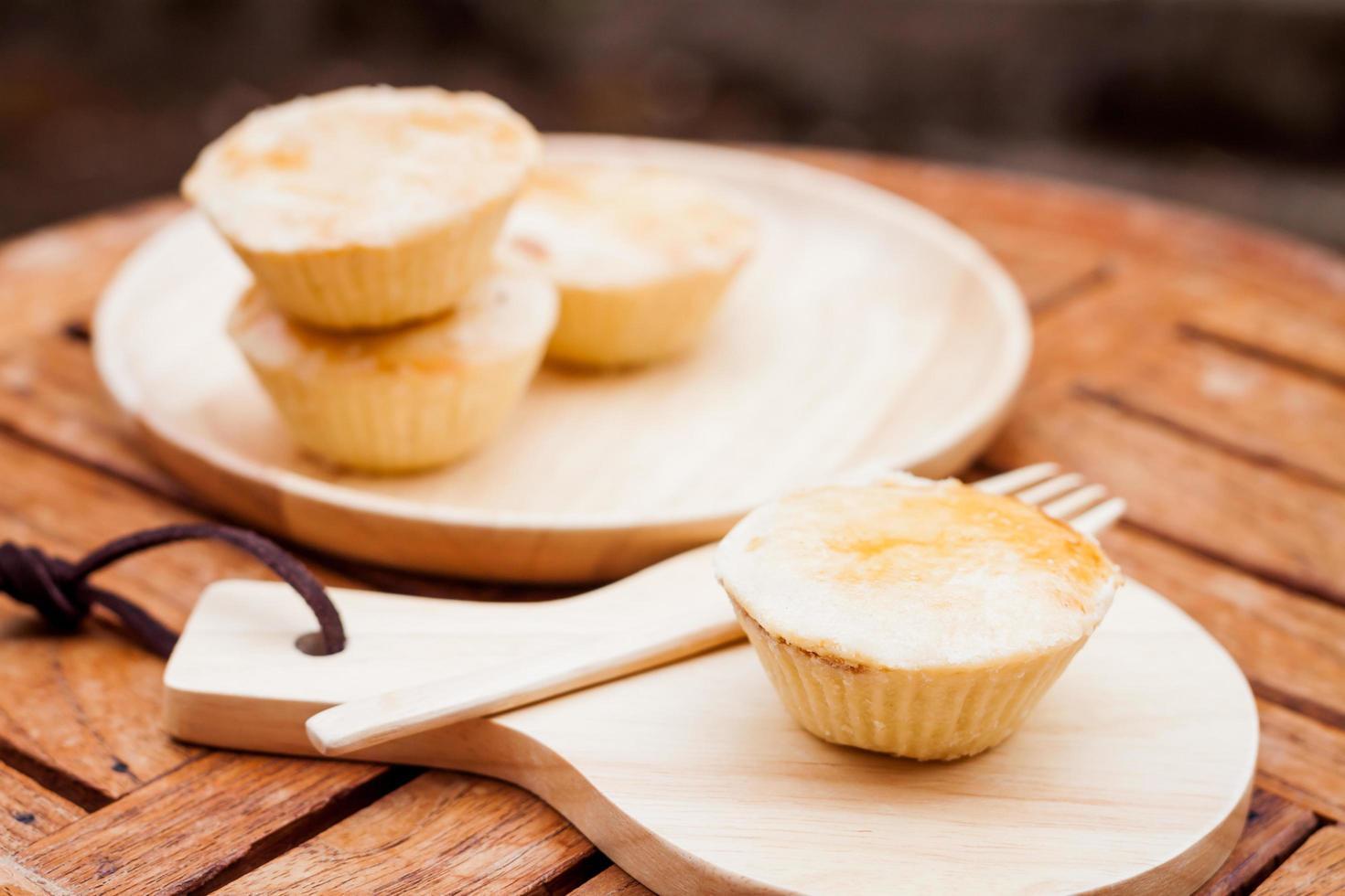 mini torte su un piatto e un vassoio di legno foto