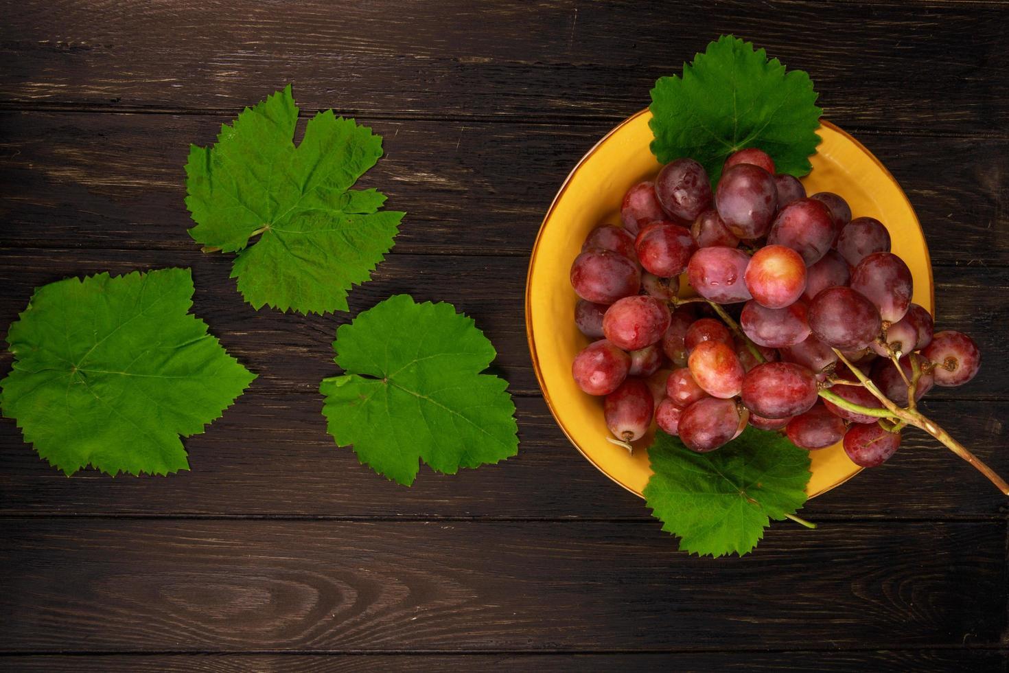 vista dall'alto di una ciotola di uva e foglie foto