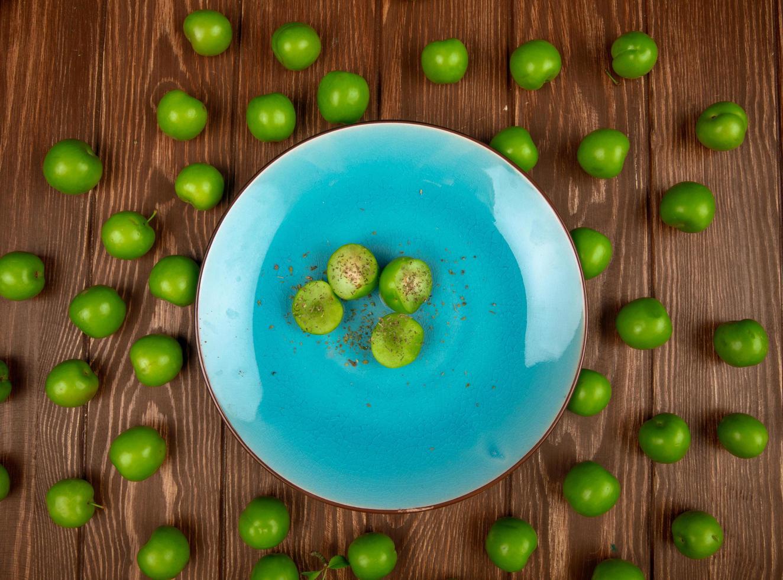 vista dall'alto di un piatto blu con prugne verdi su uno sfondo di legno foto