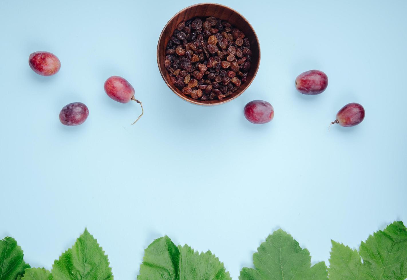 vista dall'alto di una ciotola di uvetta con uva su sfondo blu foto