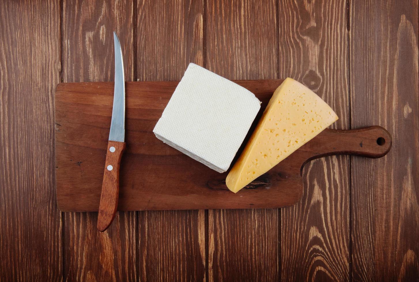 vista dall'alto di pezzi di formaggio con un coltello da cucina su un tagliere di legno foto