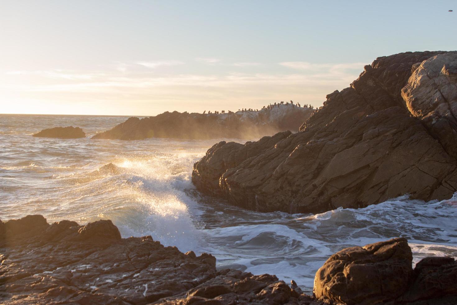 onde che si infrangono sulle rocce in una spiaggia foto