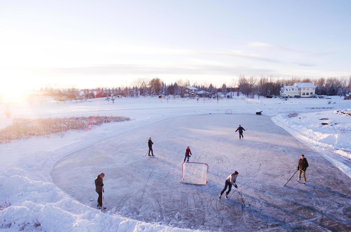 gruppo di persone che giocano a hockey all'aperto durante l'inverno foto
