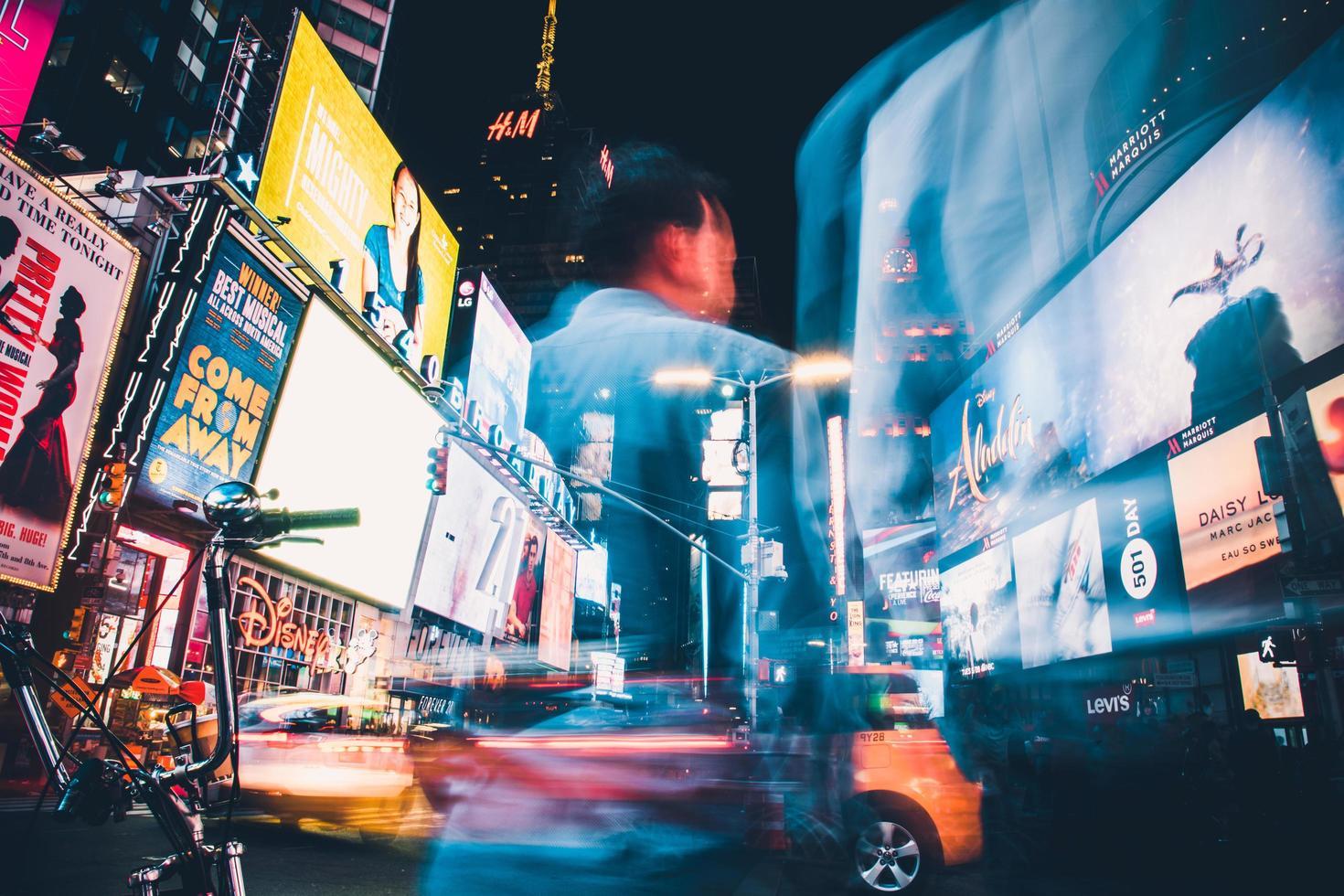 uomo in camicia blu in piedi vicino alle auto durante la notte foto