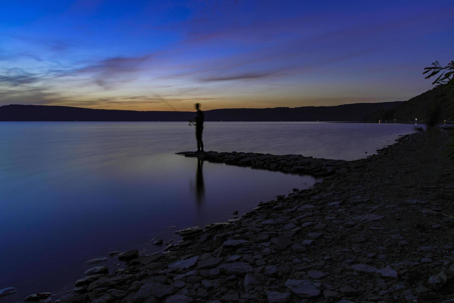 uomo in piedi sulla riva del mare foto